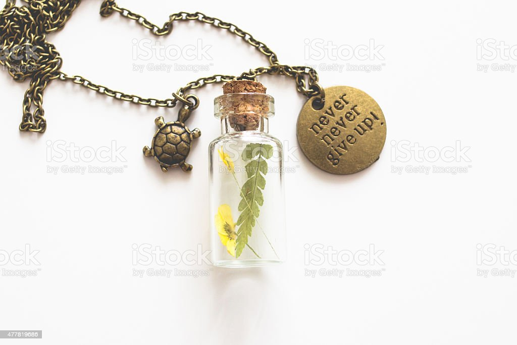 Brass pendant with dry flowers in tiny bottle stock photo
