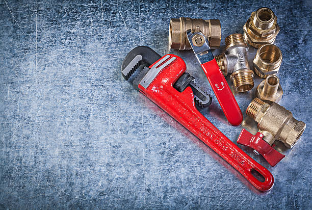 Brass pipe connectors monkey wrench on metallic background plumb Brass pipe connectors monkey wrench on metallic background plumbing concept. coupling device stock pictures, royalty-free photos & images
