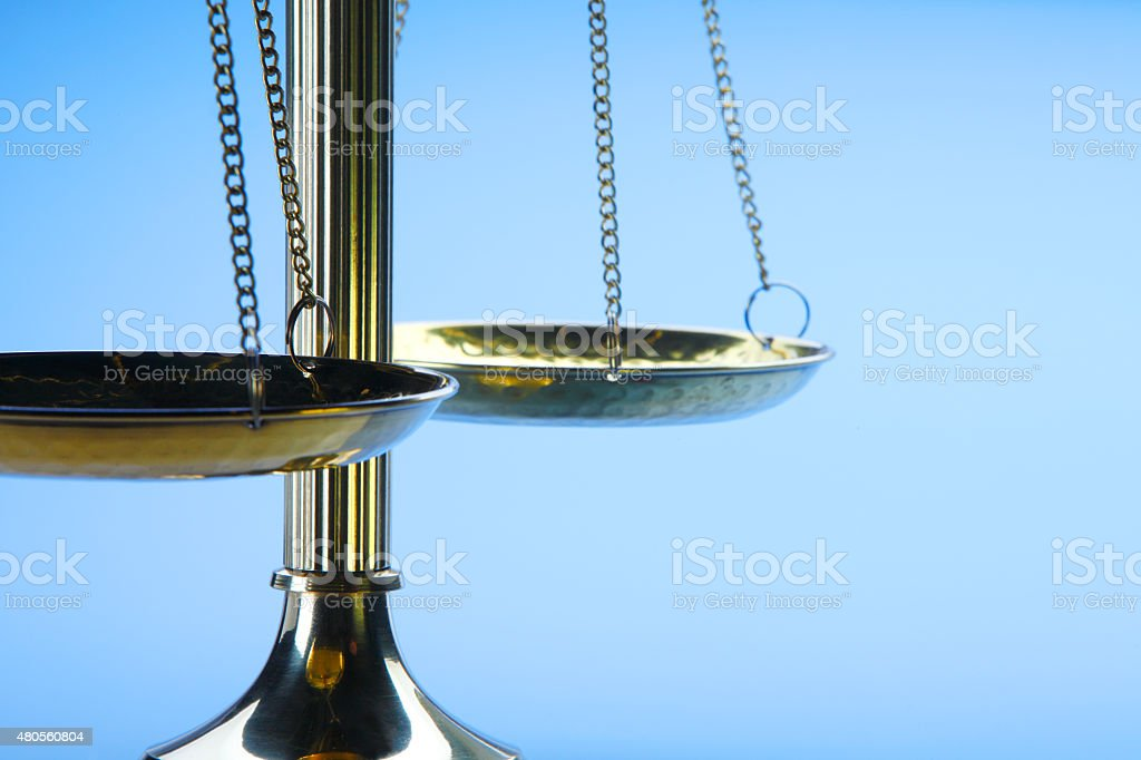Brass Scales Of Justice On A Blue Background stock photo
