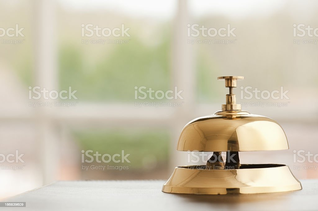 Brass service bell sitting on a reception desk beside window stock photo