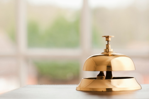Brass Service Bell Sitting On A Reception Desk Beside Window Stock Photo - Download Image Now