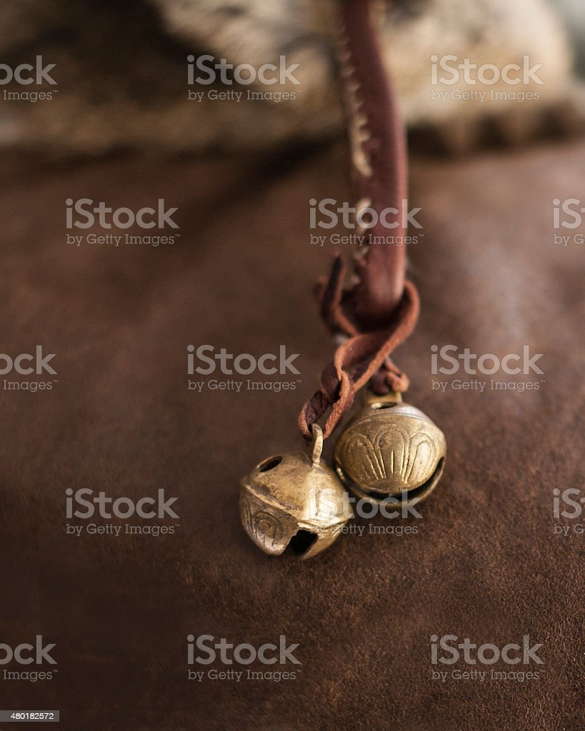 Brass Sleigh Bells Against Leather Hide stock photo