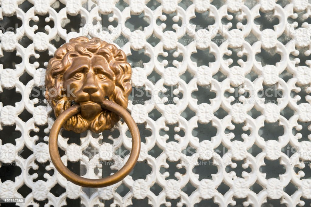 brass vintage lion head door ring, knocker against white wall background with patterns stock photo