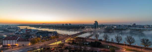 bratislava mit donau bei sonnenaufgang mit nebel über dem fluss. - bratislava hotel stock-fotos und bilder