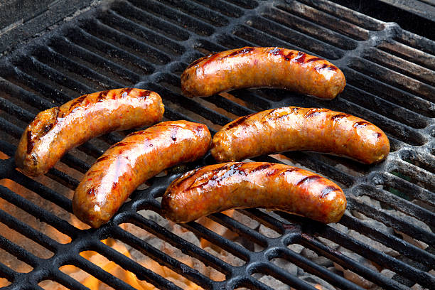 Brats Being Grilled Over A Hot Charcoal Grill stock photo