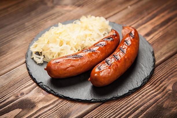bratwurst and sauerkraut on wooden table - bratwurst mit sauerkraut stock-fotos und bilder