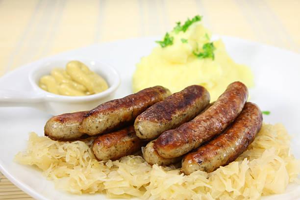 bratwurst und sauerkraut - bratwurst mit sauerkraut stock-fotos und bilder