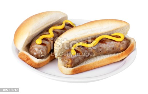 Two grilled bratwursts on buns with mustard on a plate isolated on white