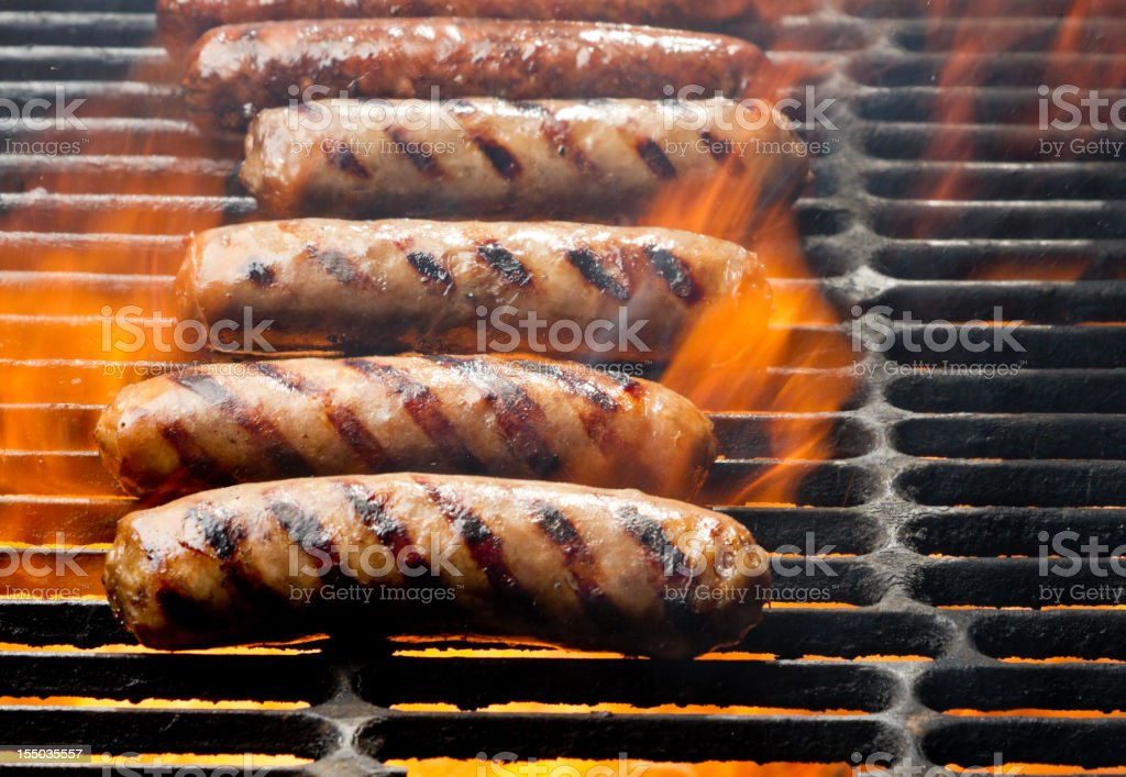 Bratwurst or Hot Dogs on Grill with Flames bildbanksfoto