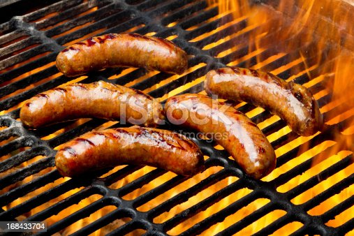 Five Plump Bratwurst or Hot Dogs on an old fashioned charcoal barbecue Grill with Flames surrounding them.