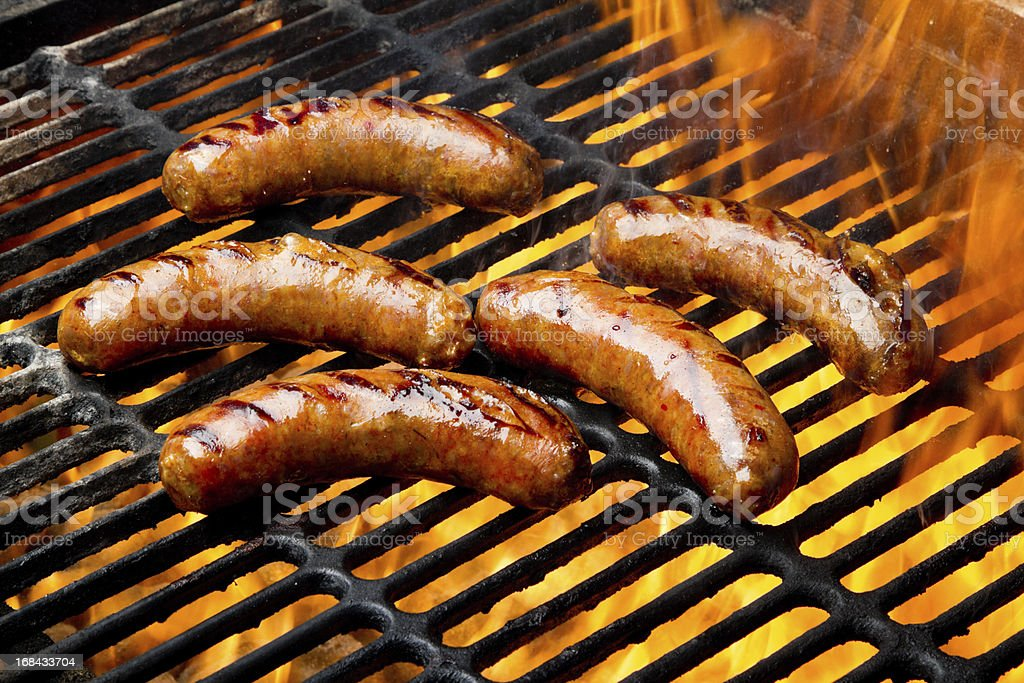 Bratwurst or Hot Dogs on Grill with Flames stock photo