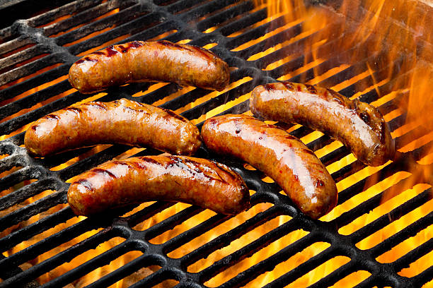 bratwurst or hot dogs on grill with flames - grilled stock photos and pictures