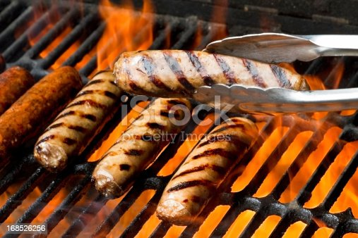 Bratwurst, hot dogs or polish sausage on a flaming charcoal grill.  One brat is being presented in a pair of tongs in front of the others.  All of them have beautiful appetizing grill marks as the flames kiss the meat sealing in the flavors.