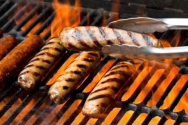 bratwurst or hot dogs on grill with flames - sausage stock photos and pictures