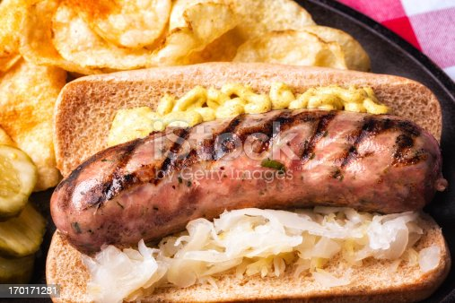 Brat with mustard, chips pickles, and saurkraut