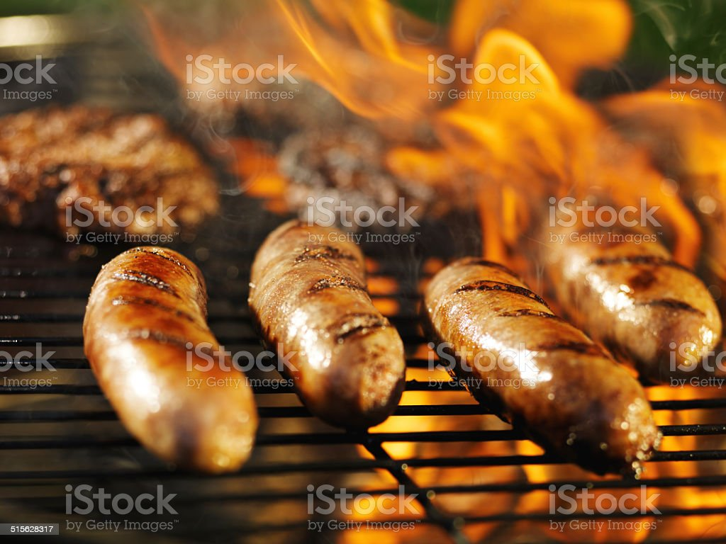 bratwursts cooking over fire on barbecue grill stock photo