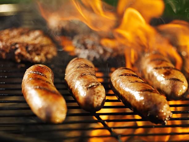 bratwursts gotowania na ogień na grill - kiełbasa zdjęcia i obrazy z banku zdjęć