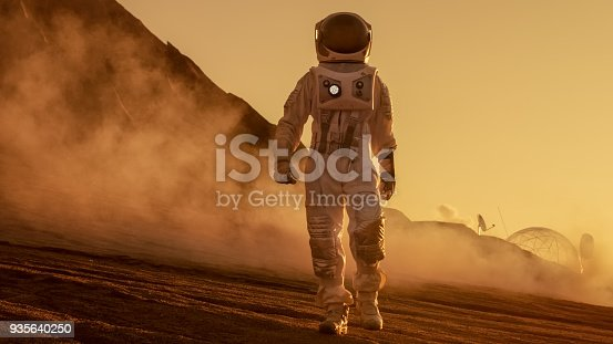 istock Brave Astronaut Confidently Walks on Mars Surface. Red Planet Covered in Gas and rock,  Overcoming Difficulties, Important Moment for the Human Race. 935640250
