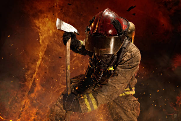 Brave Firefighter Battles Fire Firefighter surrounded by flames battles a fire while using an axe. smoke jumper stock pictures, royalty-free photos & images