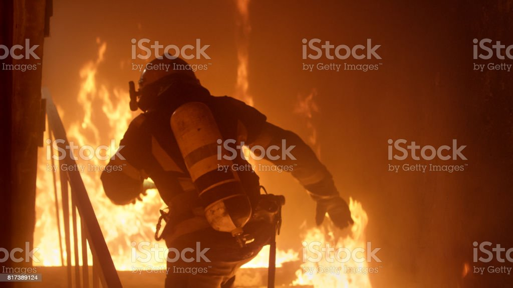 Brave Firefighter Runs Up The Stairs. Raging Fire is Seen Everywhere. stock photo