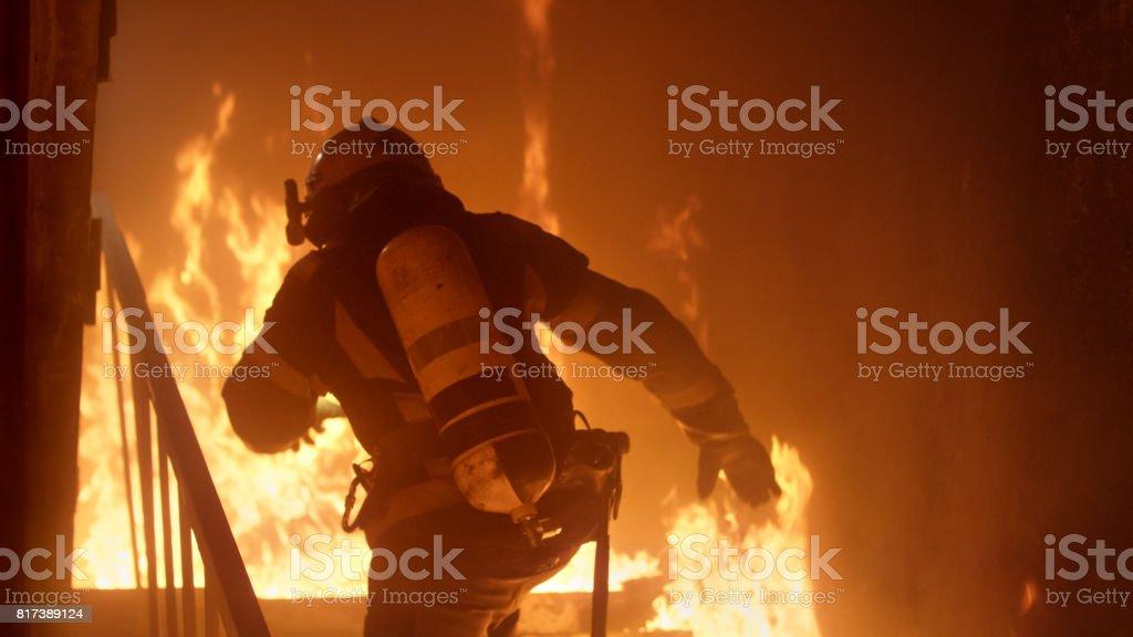 Tapferer Feuerwehrmann läuft die Treppe hinauf. Feuersbrunst ist überall zu sehen. – Foto