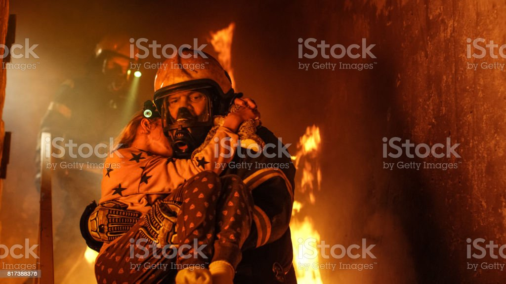 Brave Fireman Descends Stairs of a Burning Building and Holds Saved Girl in His Arms. Open fire and one Firefighter in the Background. stock photo
