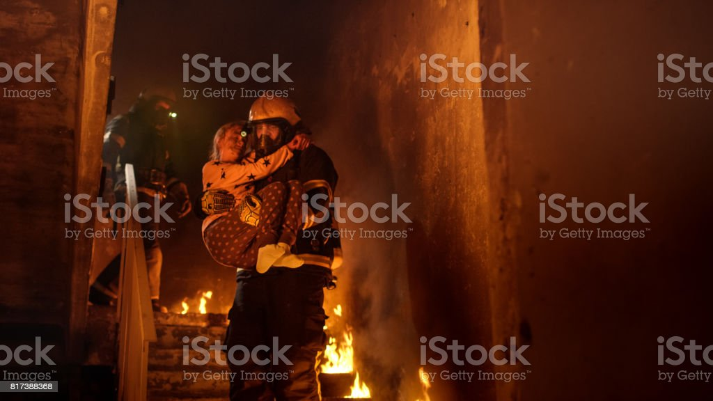 Brave Fireman Descends Stairs of a Burning Building with a Saved Girl in His Arms. stock photo