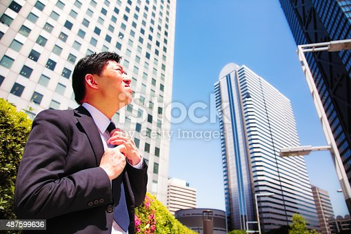Brave Japanese businessman adjusts necktie before going to work. He is looking up at the tall buildings with apprehension. Photographed in Shinjuku, Tokyo, Japan.