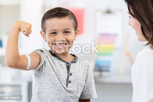 An adorable elementary age little boy sits in his unrecognizable pediatrician's office.  He smiles for the camera as he flexes his arm muscles.  There is a bandage on his arm.  His pediatrician smiles at him.