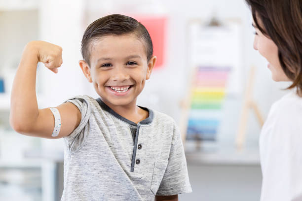 Brave little boy shows off arm bandage at pediatrician stock photo