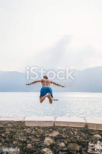istock Brave man diving in the water from a cliff. 599269474