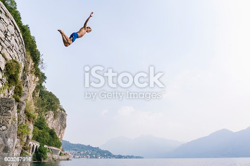 istock Brave man diving in the water from a cliff. 603267916