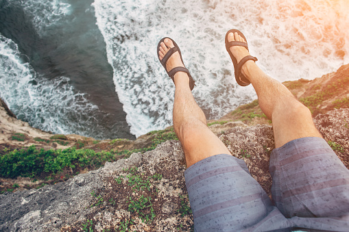 Brave man sitting on a high cliff above ocean