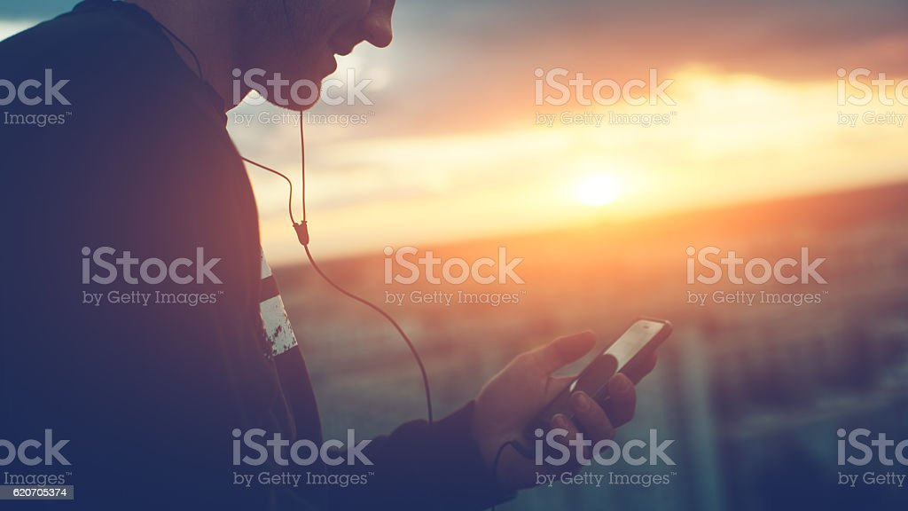 Brave man with smartphone listening music on the roof stock photo