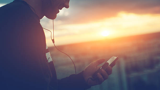 brave man with smartphone listening music on the roof - auriculares equipo de música fotografías e imágenes de stock