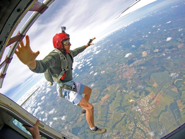 Brave Parachutist with red helmet jump out of the plane stock photo