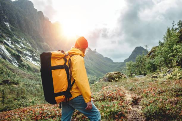 Mutiger Tourist trägt gelbe Jacke mit Reiserucksack Wandern in den Bergen Outdoor-Reise. Aktive sreiselustige Sendelust – Foto