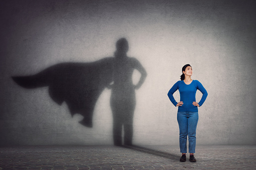 istock Brave woman keeps arms on hips, smiling confident, casting a superhero with cape shadow on the wall. Ambition and business success concept. Leadership hero power, motivation and inner strength symbol. 1183903175