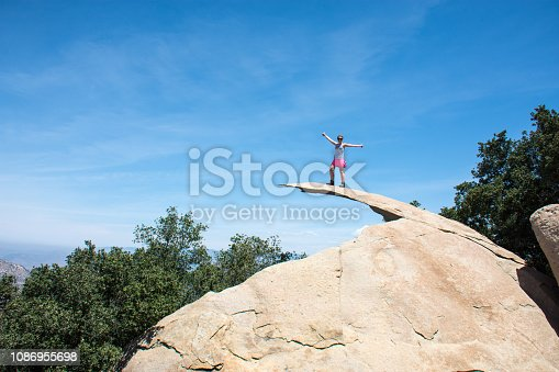Brave young adult woman hiker stands on top of Potato Chip Rock in San Diego California
