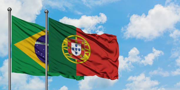 Bandeira de Brasil e de Portugal que acena no vento de encontro ao céu azul nebuloso branco junto. Conceito da diplomacia, relações internacionais. - foto de acervo