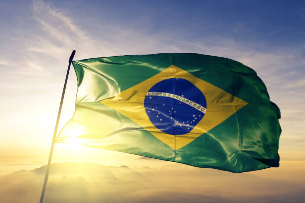 brazil brazilian flag textile cloth fabric waving on the top sunrise mist fog - independence stock photos and pictures