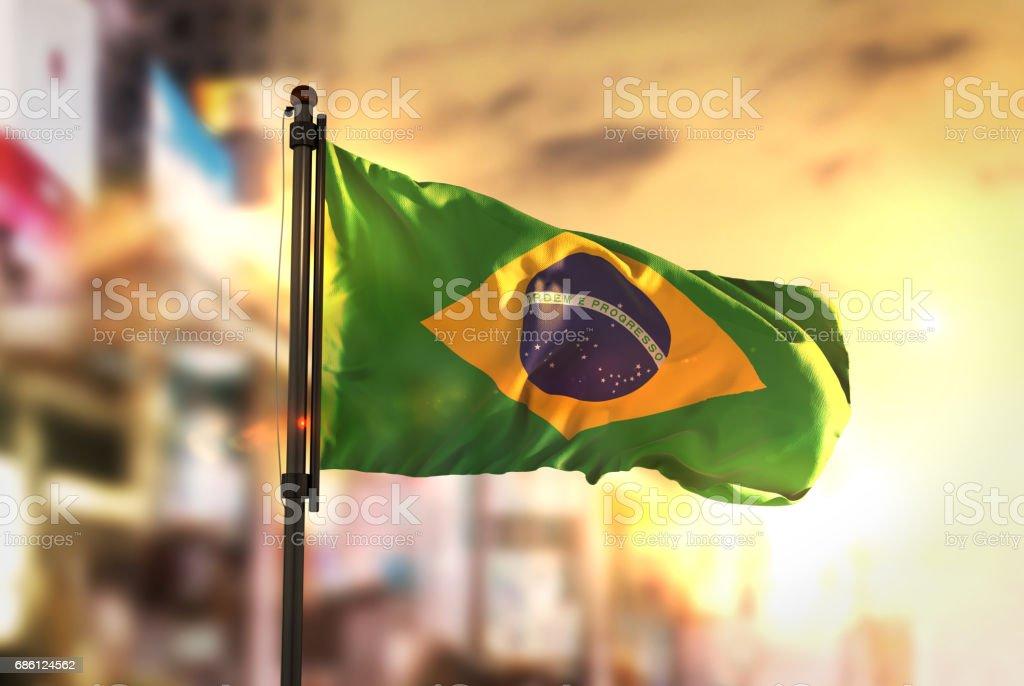 Brasilien-Flagge gegen City unscharf Hintergrund bei Sonnenaufgang Hintergrundbeleuchtung – Foto