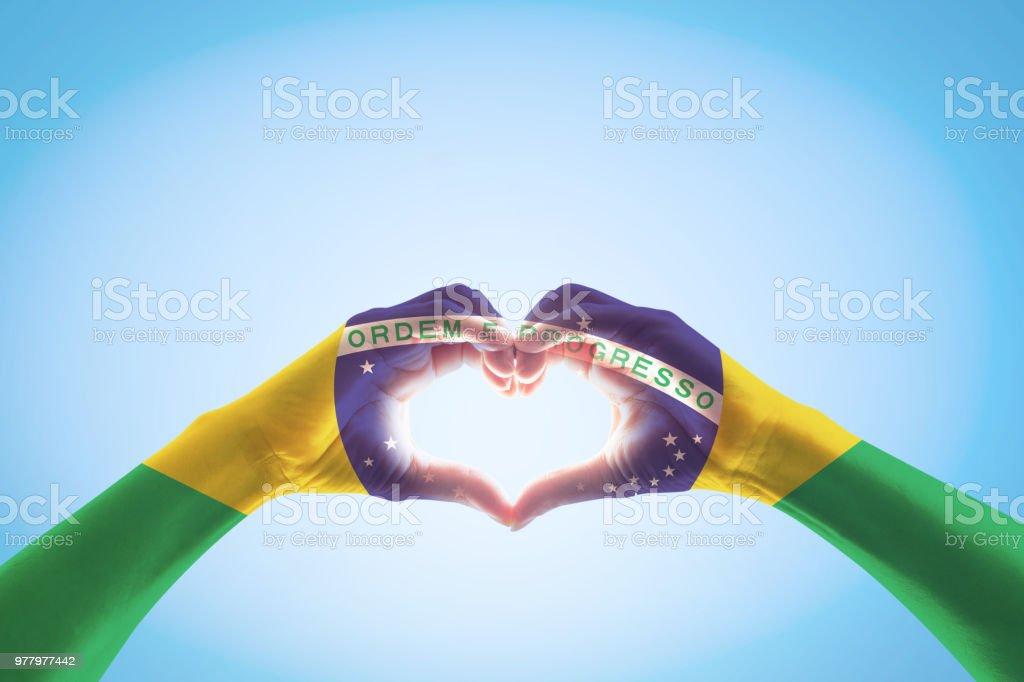 Brasilien-Flagge auf Menschen Hände in Herzform für Labor Day und Nationalfeiertag feiern auf blauen Himmelshintergrund isoliert – Foto