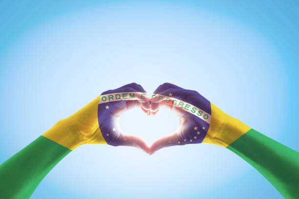 brazil flag on people hands in heart shape for labor day and national holiday celebration isolated on blue sky background - independence stock photos and pictures