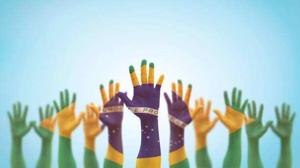 ボランティア、投票、助け、そして青空の背景に孤立したブラジルの力のために祈る国民の祝日のお祝いのために上げる人々の手のひらのブラジルの旗(クリッピングパス) - 独立 ストックフォトと画像