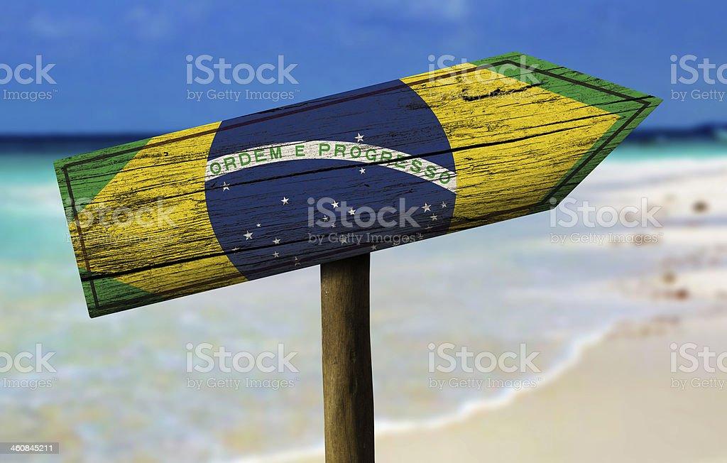 Bandeira do Brasil, com uma placa de madeira na praia no fundo - foto de acervo