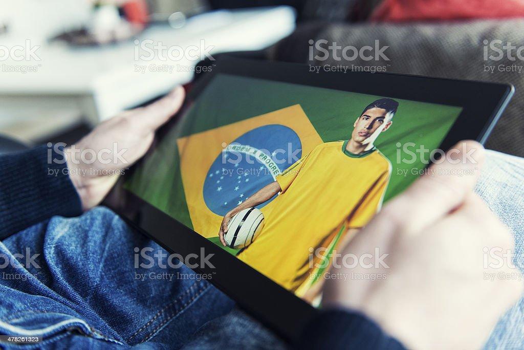 Jogador de futebol do Brasil em tablet digital com uma bola - foto de acervo