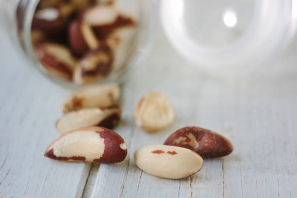 Brazil nuts and glass bottle over the white table stock photo
