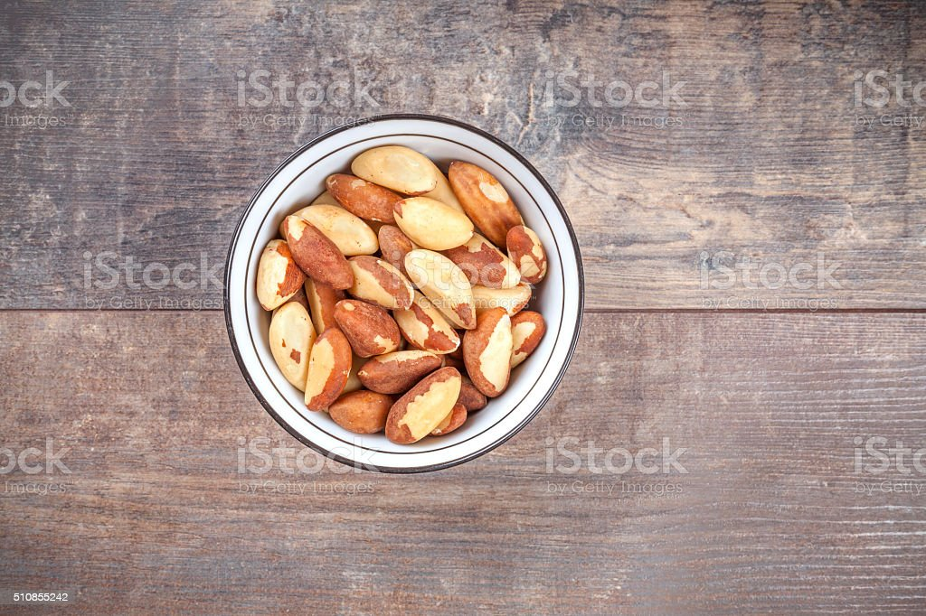 Brazil nuts in a bowl on wooden background stock photo