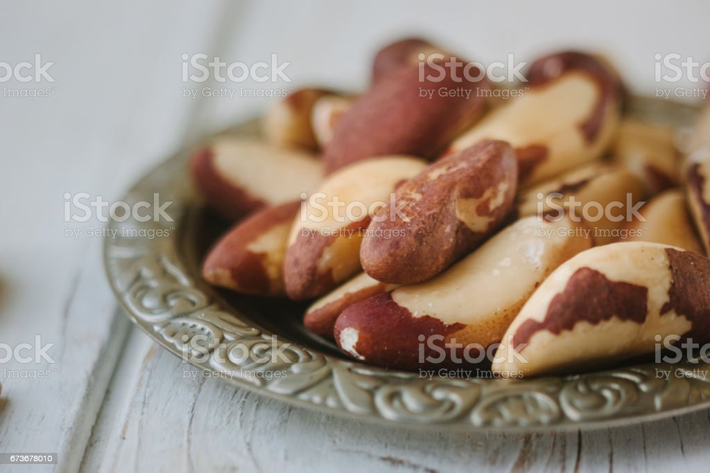 Brazil nuts in metal plate over the white wooden table. stock photo
